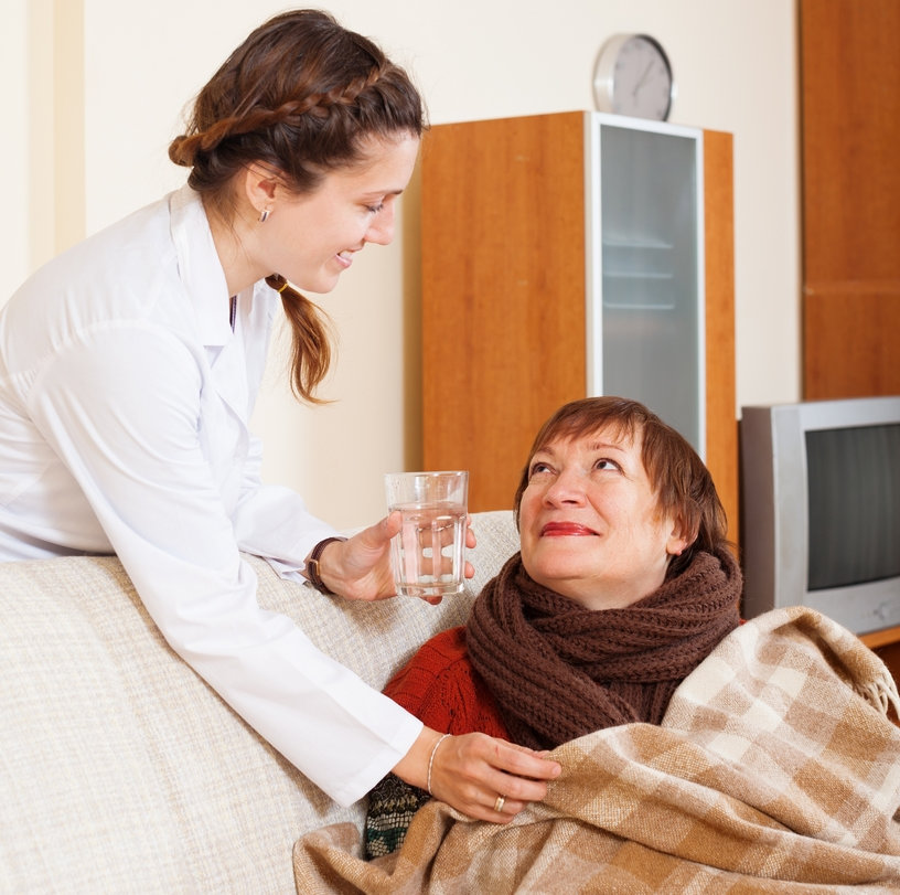 caregiver giving her paitent her medication